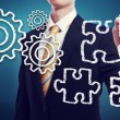 Stock Photo: Business Mwith Gears and Puzzle Pieces