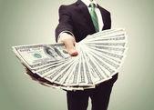 Geschäftsmann, die darstellung einer verbreitung von bargeld — Stockfoto