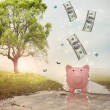 Stock Photo: Dollar bills falling in or flying out of a piggy bank in a magical landscape