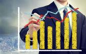 Affärsman med diagram som representerar tillväxt — Stockfoto