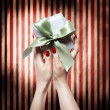 Hand with red nails holding a gift box — Stockfoto