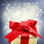Golden gift box with big red ribbon — Stock Photo