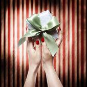 Hand with red nails holding a gift box — Photo