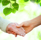 Holding hands with senior — Stock Photo
