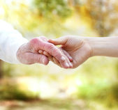 Holding hands with senior — Stockfoto