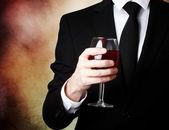 Mladý muž, který držel sklenici červeného vína — Stock fotografie