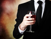 Young man holding a glass of red wine — Stok fotoğraf