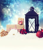 Christmas lantern with ornaments in the snow — Stock Photo