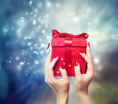 Red present box held up by in a woman's hands — Stockfoto