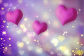 Pink hearts on purple background — Stock Photo