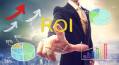 Businessman touching ROI (return on investment) — Stock Photo