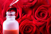 Dropper bottle with red roses — ストック写真