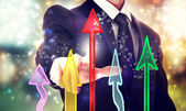 Businessman pointing rising arrows — Stock Photo