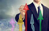Businessman drawing rising arrows — Stockfoto