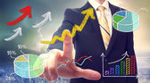 Businessman pointing at rising arrows — Stockfoto