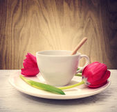 Coffee cup with red tulips — Stock fotografie