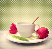 Coffee cup with red tulips — Stock Photo