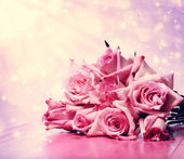 Beautiful pink roses on pink wooden table — Stock Photo