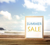 Summer sale sign over ocean and sky — Stock Photo