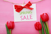 Spring sale sign with red tulips — Stock Photo
