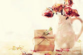 Dried roses in vase with gift box — Stock Photo