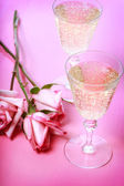Two champagne glasses with pink roses — Stock Photo