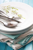 A stack of clean white plates with sliverware — Stock Photo