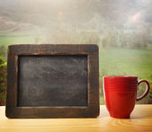 Chalkboard with red mug — Stock Photo