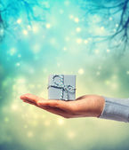 Presenting a small blue gift box — Stock Photo