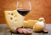 Red wine with cheese selection and salami — Stock Photo