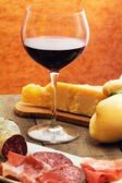 Selection of cheese and ham with glass of red wine — Stock Photo