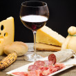 Stock Photo: Selection of cheese and ham with glass of red wine