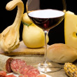 Cheese, ham and wine with autumnal decorations — Stock Photo