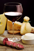 Selection of dairy product, salami and red wine — Stock Photo