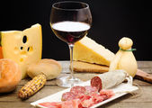 Selection of cheese and ham with glass of red wine — Stok fotoğraf