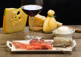 Selection of dairy product, salami, Parma ham and red wine — Stock Photo