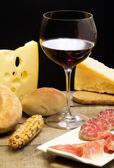 Süt ürünleri, salam, parma jambonu ve kırmızı şarap seçimi — Stok fotoğraf