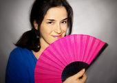Atraktivní tmavovláska s růžovými ventilátorem — Stock fotografie