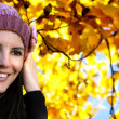 Smiling girl with wool hat against autumnal background — Photo