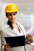 Vrouwelijke architect tegen interieurs achtergrond — Stockfoto
