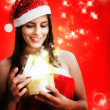 Girl dressed santa claus opens magic box — Stok fotoğraf