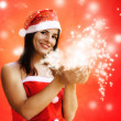 Female santa claus with sparkling stars — Stock Photo