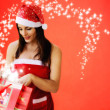 Beautiful girl dressed santa claus opend christmas gift — Stock Photo #16078645