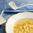 Broth with ravioli over blue linen tablecloth — Foto Stock