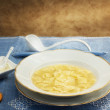 Broth with ravioli over blue linen tablecloth — Photo
