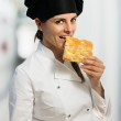 Female chef  biting a focaccia slice — Stok fotoğraf