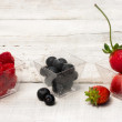 Red fruits over white wood — Stock Photo
