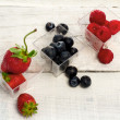 Red fruits over white wood — Stockfoto