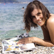 Beautiful girl at the beach with gossip journal — Foto Stock