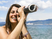 Beautiful girl at the beach with funny spyglass — Stock Photo